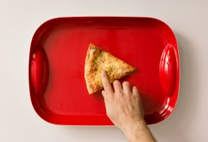 Pizza cut on red tray with hand. Flat lay